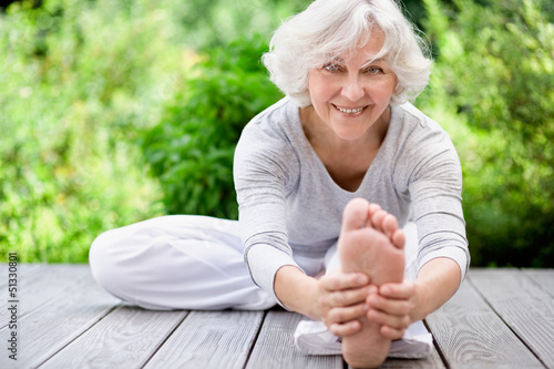 Leinwanddruck Bild Sportliche Seniorin beim Streching