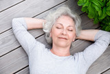 grauhaarige Frau entspannt auf der Terrasse