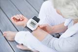 Fototapety grauhaarige Frau misst idealen Blutdruck