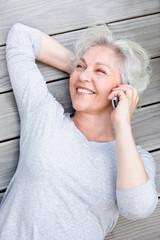Attraktive, grauhaarige Frau telefoniert