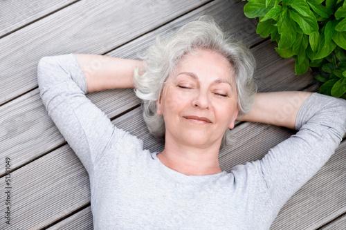 Leinwanddruck Bild grauhaarige Frau entspannt auf der Terrasse