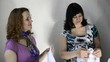 Three pregnant women are looking clothes for babies
