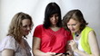 Three pregnant women look at photos of the smartphone