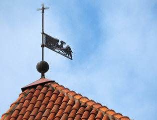 Vintage weather vane bird on the red roof