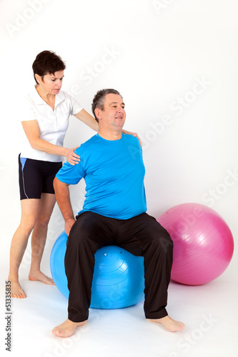 Woman helping man with exercise ball during the exercise