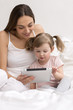 Child using tablet with her mother