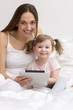 Little girl using tablet with her mother smiling