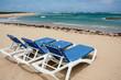 calm beach with deckchairs under the blue sky