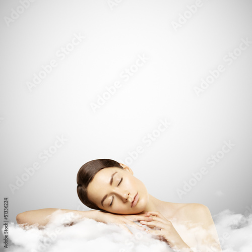 Portrait of a young girl sleeping on a cloud