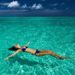 Woman in bikini lying on water