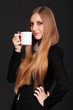 Cute young business woman holding coffee cup isolated in black b