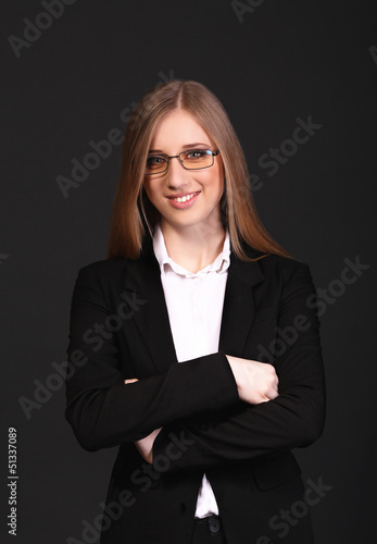 Beautiful young business woman isolated in black background