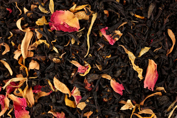aromatic black dry tea with fruits and petals, close up