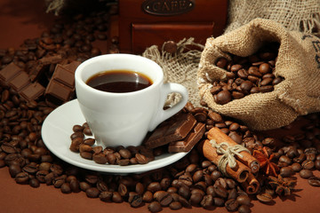 cup of coffee and coffee beans on brown background