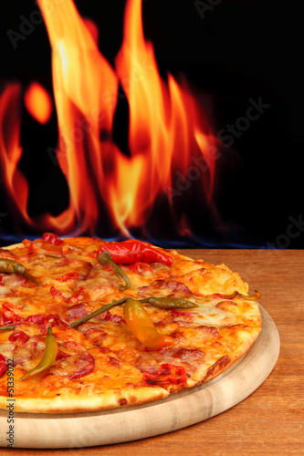 Tasty pepperoni pizza on wooden board on flame background