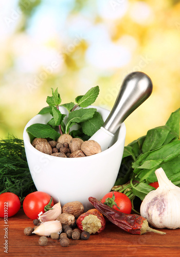 Composition of mortar,spices, tomatoes and  green herbs,