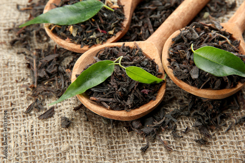 Dry tea with green leaves in wooden spoons, on burlap