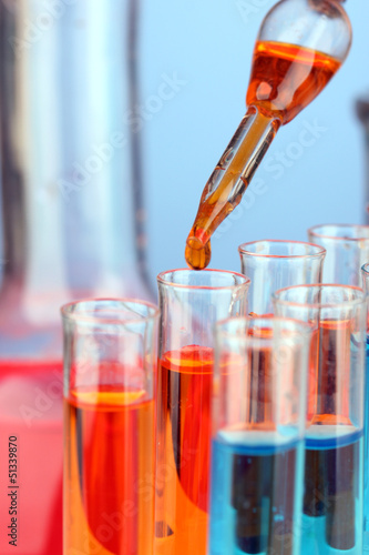 Laboratory pipette with drop of color liquid over glass test