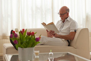 Senior man with glasses reading book in living room.