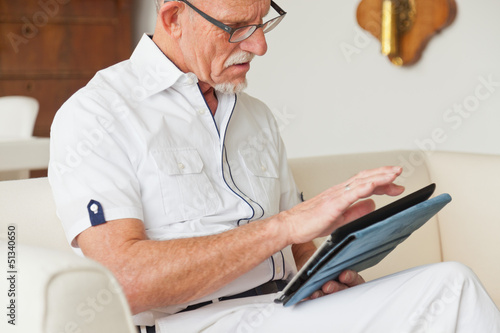Senior man with glasses using tablet on couch in living room.