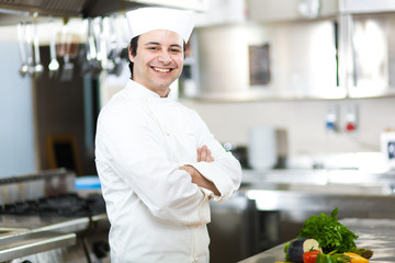Chef with arms crossed in restaurant kitchen