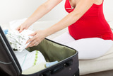 Fototapety Pregnant woman packing baby clothes