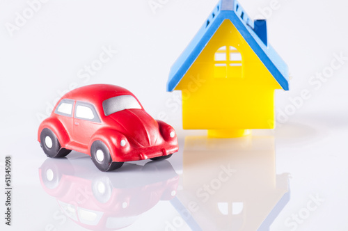 small red toy beetle car and house on white with reflection