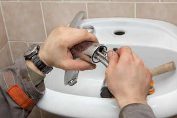 Plumber work, fixing water tap in a bathroom