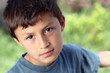 Serious young boy outside with copy space to right