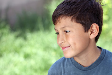 Smiling young boy outside with copy space to left