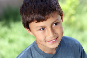Smiling young boy outside with copy space