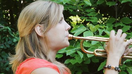Female musician playing a trumpet. Sunny morning outdoors.