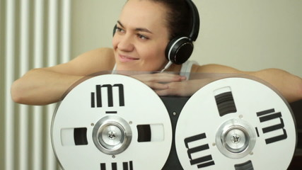 Girl listening to music from retro tape recorder, slow motion