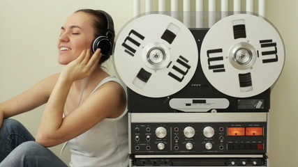 Girl listening to music from retro audio tape recorder