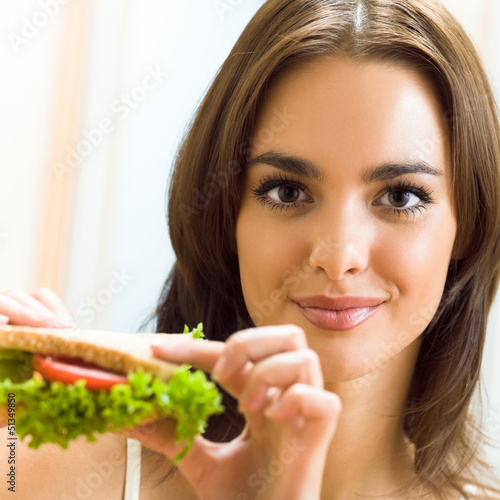Happy smiling woman with sandwich at home