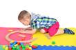 Kleinkind baut mit Holzschienen einen Kreis