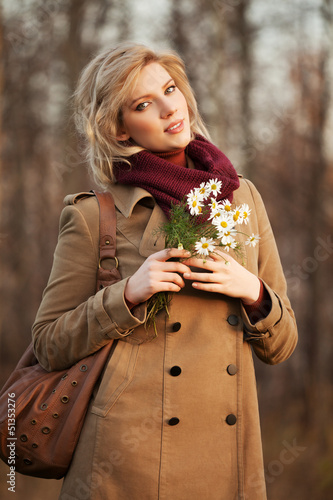 Young woman with a flowers in autumn forest