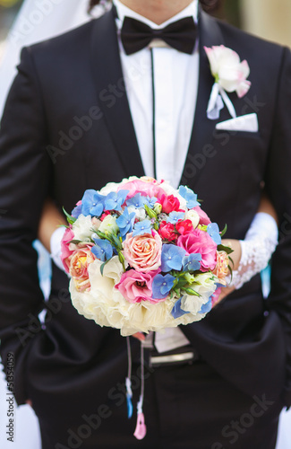 Wedding bouquete of bride colorful flowers on drass