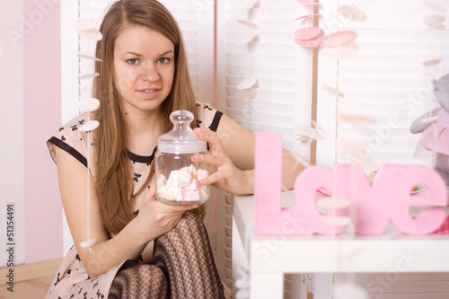 girl holding a jar of marshmallow