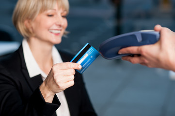 Corporate lady swiping her card to pay