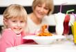 Cute kid enjoying pasta and juice