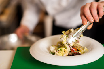 Chef arranging tossed salad in a white bowl