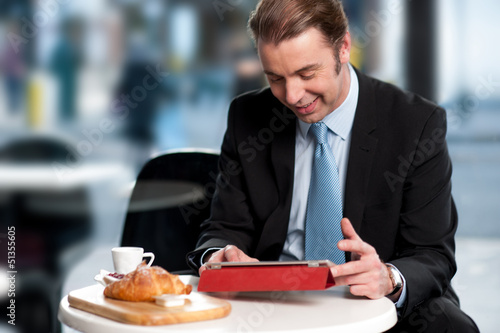 Male manager browsing internet on tablet device