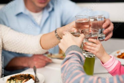 Leinwandbild Motiv Family toasting water glasses in celebration