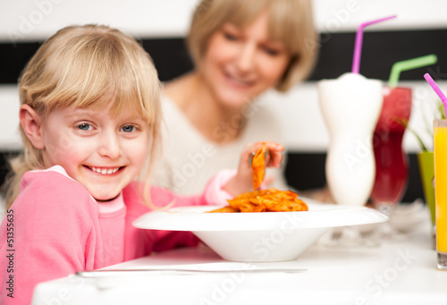 Cute kid enjoying pasta and juice