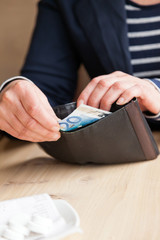 Woman's hands taking money out of wallet. Paying the bill.