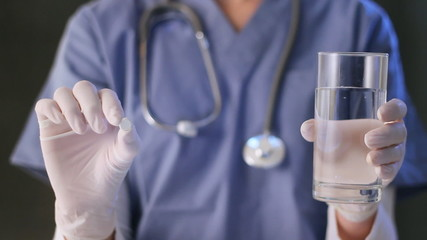 Doctor holds up a pill and glass of water.