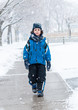 Hispanic Child Walking in the Sidewalk on a Snowy Day