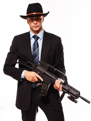 man in suit and hat with weapon in hands