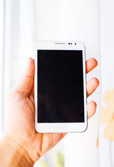 male hand is holding white phone